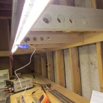 The temporary LED strip mounted up on the benchwork with a clamp.